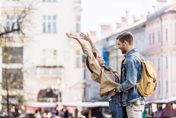 Boyfriend and girlfriend looking at each other and smiling in city - Photo, Image