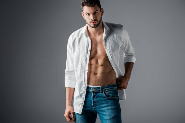 sexy brunette man in white shirt and jeans on grey - Photo, Image