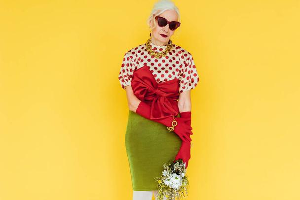 Beautiful elderly woman in sunglasses holding bouquet of wildflowers isolated on yellow - Photo, Image