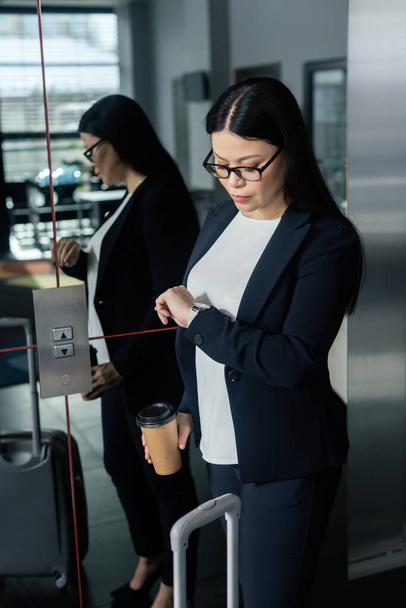 ázsiai üzletasszony papír pohár nézi karóra és a lift közelében áll   - Fotó, kép