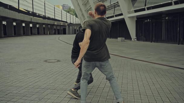 handsome men fighting on street near building  - Footage, Video