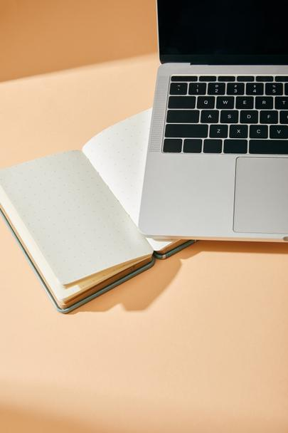 high angle view of opened blank notebook and laptop on beige background - Photo, Image