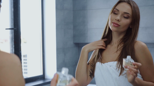beautiful young woman in bath towel applying perfume in bathroom - Footage, Video