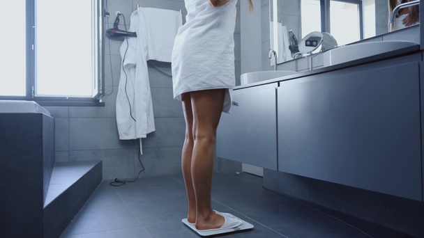 attractive young woman in bath towel walking and weighting on scales in bathroom - Footage, Video
