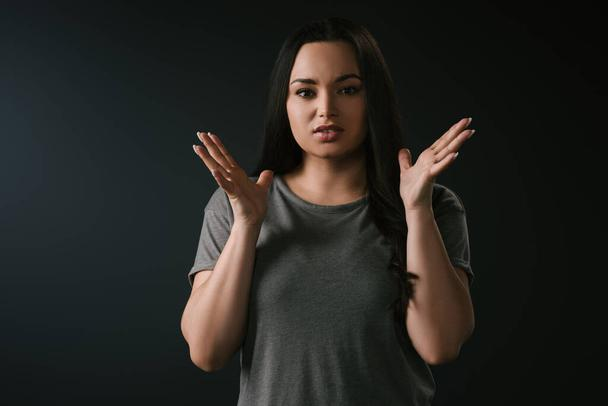 Front view of irritated plus size girl gesturing on black background  - Photo, Image