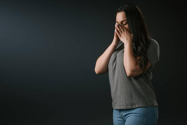 Sad plus size girl crying and covering face with hands on black background  - Photo, Image