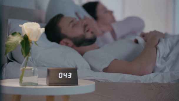 Selective focus of tired woman suffering from snoring man near clock on table - Footage, Video