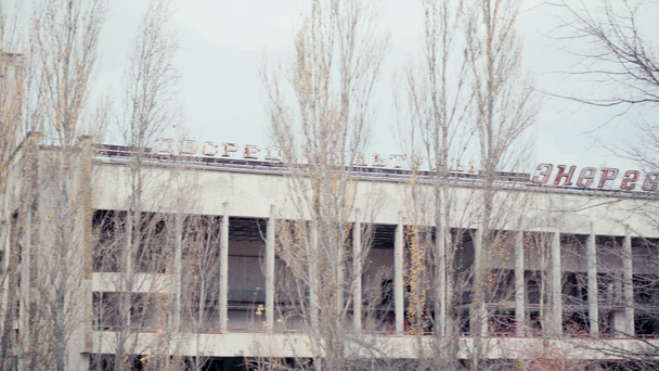 CHERNOBYL, UKRAINE - NOVEMBER 6, 2019: abandoned building with palace of culture and energetic lettering near trees  - Footage, Video