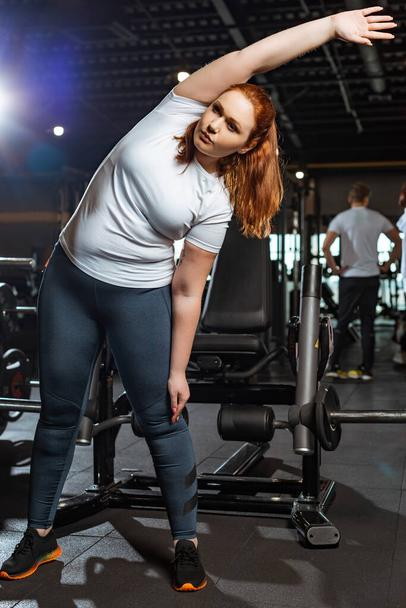 pretty, overweight girl warming up while doing side tilt exercise  - Photo, Image