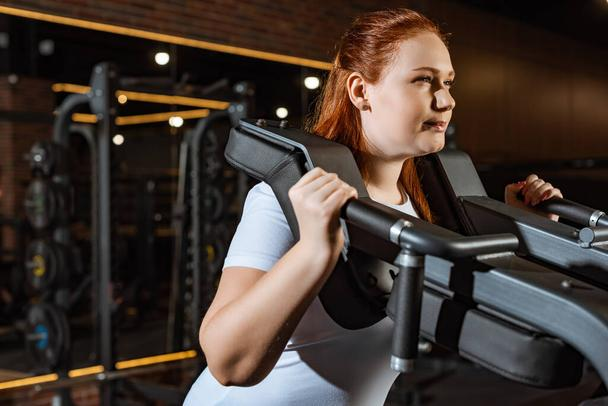 confident overweight girl doing arms extension exercise on fitness machine - Photo, Image
