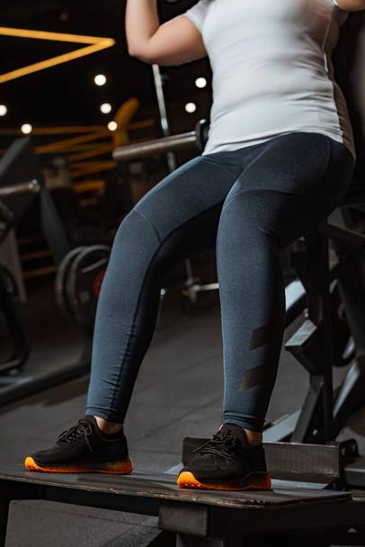 cropped view of overweight girl training on fitness machine - Photo, Image