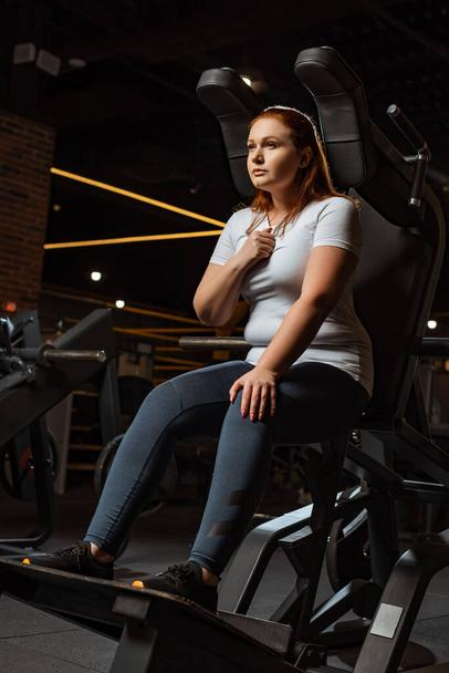 confident overweight girl looking away while sitting on fitness machine - Photo, Image