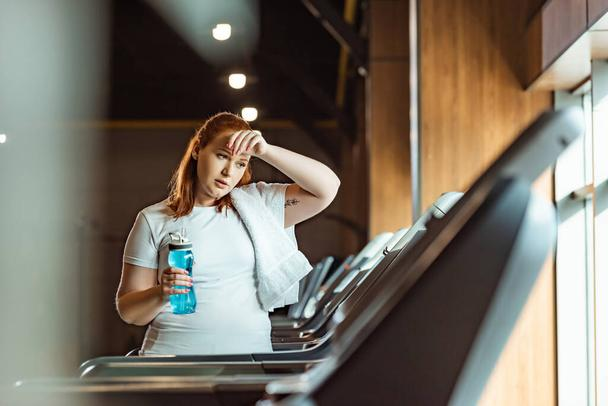 selective focus of tired overweight girl touching forehead and holding sports bottle while standing at treadmill - Photo, Image