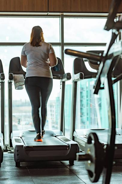 back view of overweight girl running on treadmill in gym against window - Photo, Image
