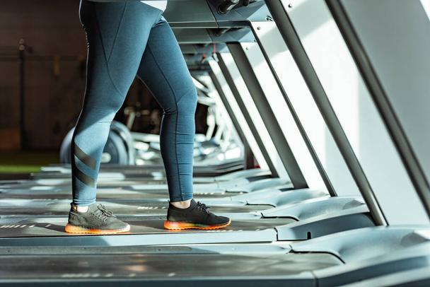 cropped view of overweight girl in leggings running on treadmill in gym - Photo, Image