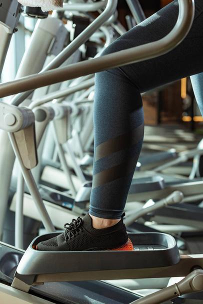 cropped view of overweight girl in leggings training on stepper in gym - Photo, Image