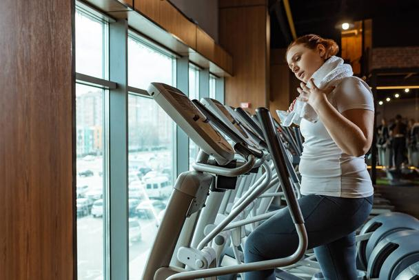 tired overweight girl touching towel while working out on stepper  - Photo, Image