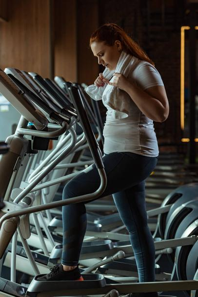 side view of focused overweight girl training on stepper while holding towel - Photo, Image