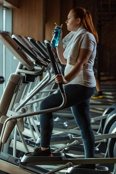 side view of overweight girl holding sports bottle while training on stepper - Photo, Image