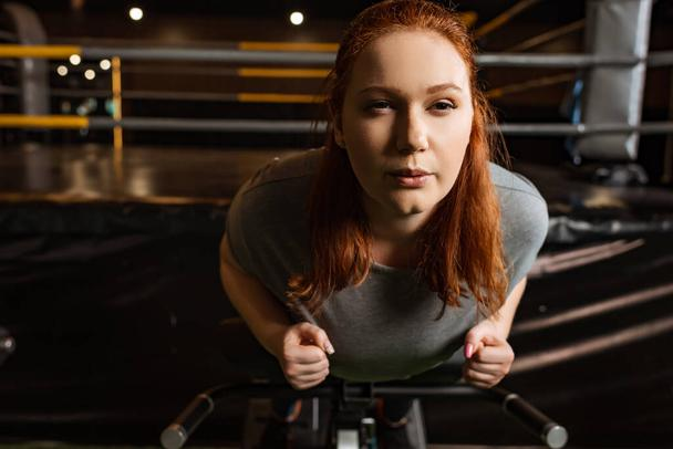 focused overweight girl doing lower back extension exercise on training machine - Photo, Image