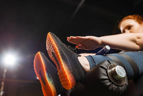 low angle view of overweight girl doing abs exercise on fitness machine  - Photo, Image