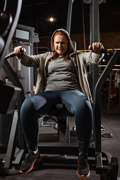 purposeful overweight girl doing arms extension exercise on fitness machine  - Photo, Image
