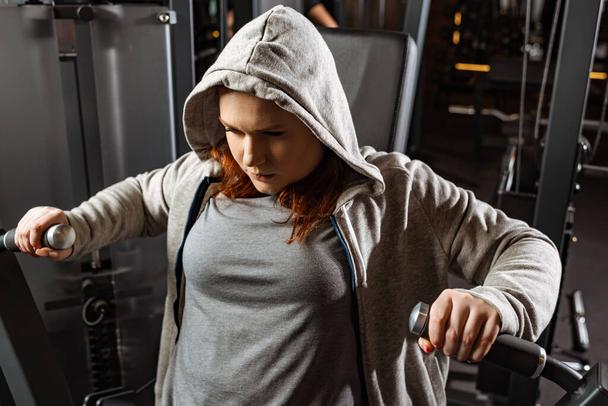 concentrated overweight girl doing arms extension exercise on fitness machine  - Photo, Image