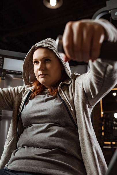 selective focus of concentrated overweight girl doing arms extension exercise on fitness machine  - Photo, Image