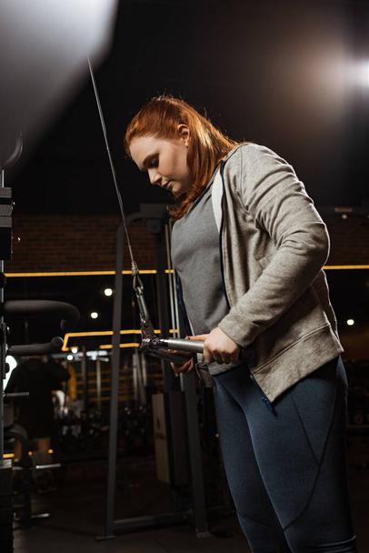 focused overweight girl doing arms extension exercise on fitness machine - Photo, Image