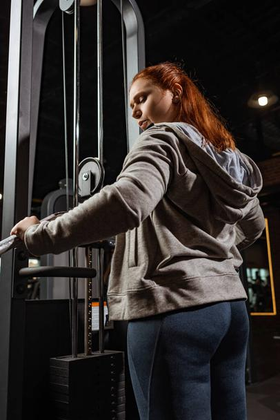 overweight girl in grey hoodie doing arms extension exercise on fitness machine - Photo, Image