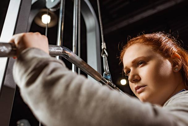 selective focus of confident overweight girl doing arms extension exercise on fitness machine - Photo, Image