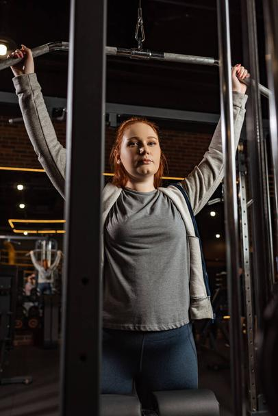 overweight girl looking at camera while doing arms extension exercise on fitness machine - Photo, Image