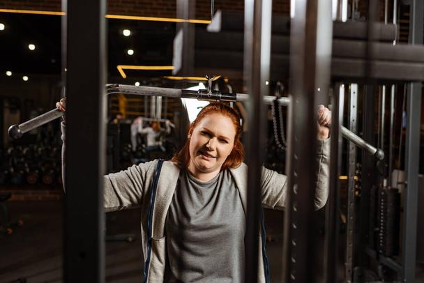 selective focus of overweight girl doing arms extension exercise on training machine - Photo, Image
