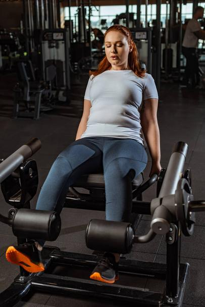 focused overweight girl doing leg extension exercise on training machine - Photo, Image
