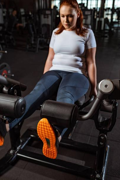 selective focus of concentrated overweight girl doing leg extension exercise on training machine - Photo, Image