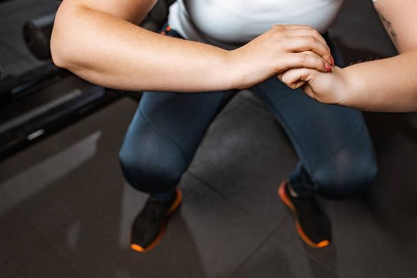 cropped view of overweight girl squatting with clenched hands in gym - Photo, Image