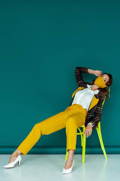 stylish woman in yellow mask and plaid blazer sitting on chair on blue - Photo, Image