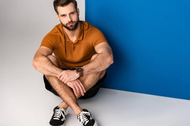 fashionable bearded man sitting in shorts and brown polo on grey and blue - Photo, Image