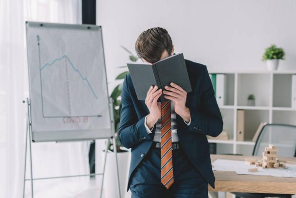 depressed businessman covering face with notebook while standing near flipchart with covid-19 inscription and infographics showing recession - Photo, Image