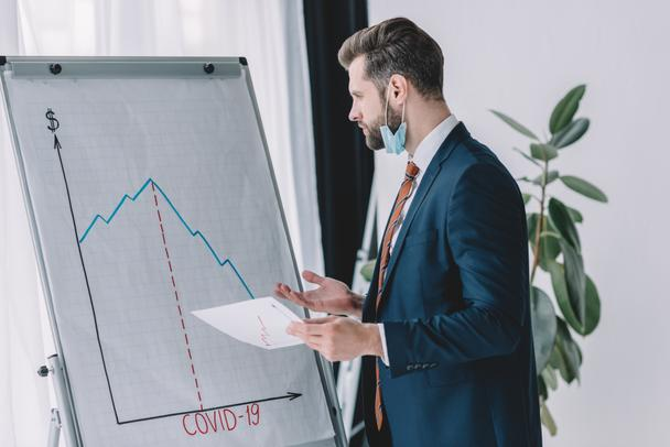 serious, thoughtful businessman holding paper while standing at flipchart with graphs showing decrease - Photo, Image