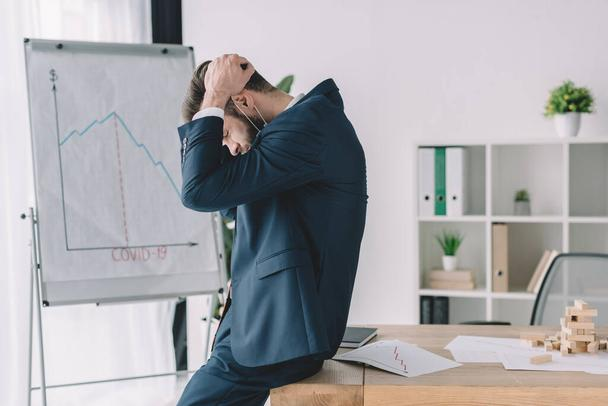 side view of depressed businessman holding hands on bowed head while near flipchart and workplace in office - Photo, Image