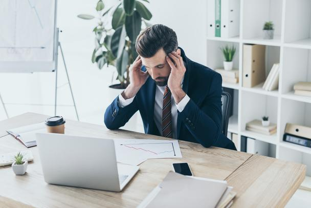 depressed businessman touching bowed head while sitting at workplace with closed eyes - Photo, Image