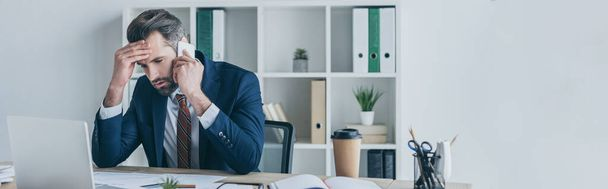 panoramic shot of upset businessman touching forehead while talking on smartphone at workplace - Photo, Image
