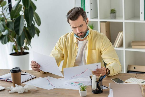 serious businessman looking at documents while sitting at workplace - Photo, Image