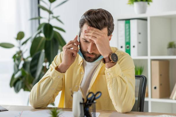 selective focus of depressed businessman touching forehead while talking on smartphone in office - Photo, Image
