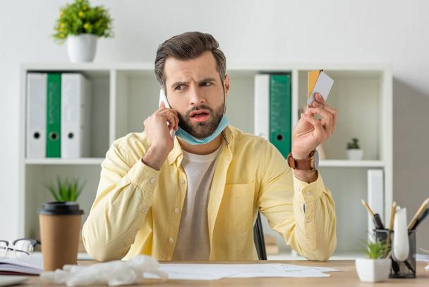 selective focus of worried businessman talking on smartphone while holding credit cards - Photo, Image