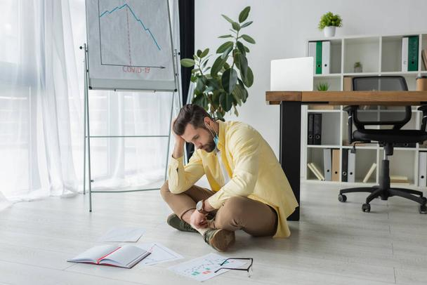depressed businessman sitting on floor near papers, notebook and flipchart with covid-19 inscription and graphs showing decrease - Photo, Image