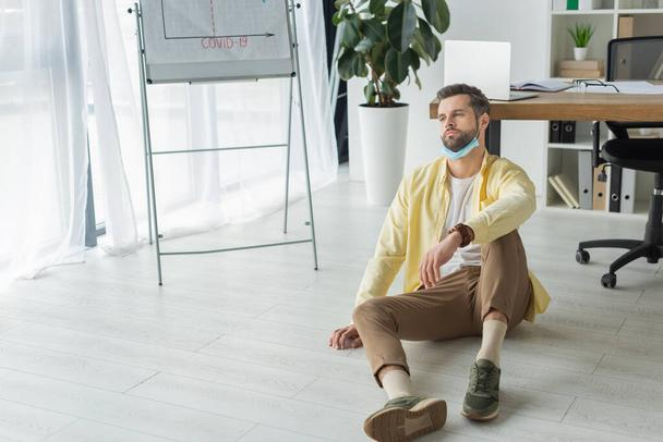 depressed businessman sitting on floor near flipchart with covid-19 inscription and looking away  - Photo, Image
