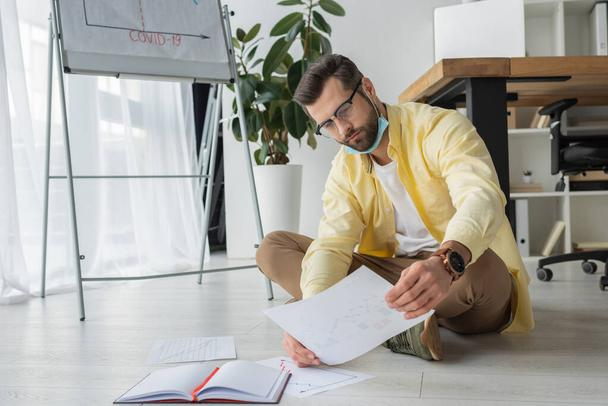 serious, thoughtful businessman looking at paper while sitting on floor near flipchart with covid-19 inscription - Photo, Image