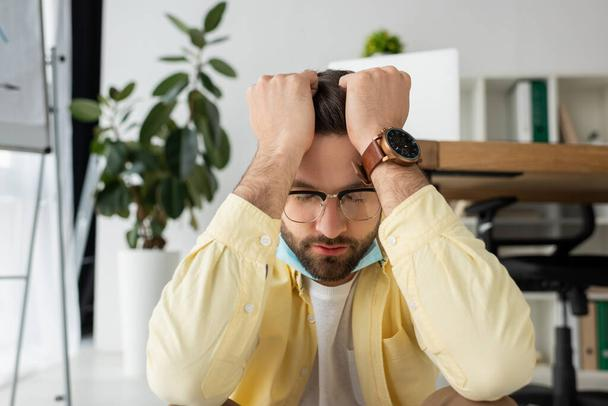depresses businessman holding hands on head while sitting in office with closed eyes - Photo, Image